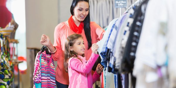 A young woman with her 7 year old daughter shopping in a clothing store. They are looking at a clothes rack.
